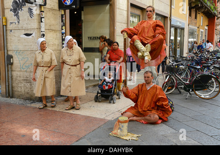 Street mime artists watched by nuns in Verona Italy - Stock Photo