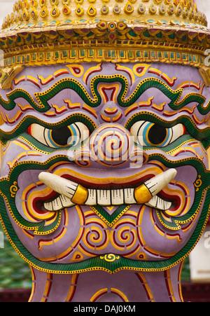 Face of giant demon (yaksha) statue guarding Wat Phra Kaew in Grand Palace in Bangkok. - Stock Photo