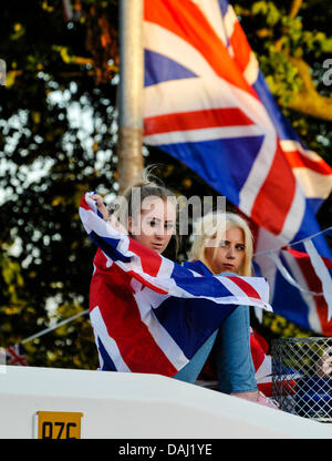 Belfast, Northern Ireland, 14th July 2013 - Two teenage girls, one draped in a Union Flag, sit on top of a PSNI - Stock Photo
