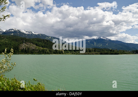 Green Lake in Whistler, British Columbia.  Whistler and Blackcomb mountains are in the distance. - Stock Photo