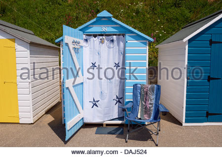 Brightly coloured beach huts with a camping chair outside on the Seafront Walk, South Devon, England