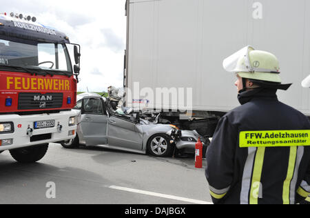 Rescue forces stand next to a car jammed underneath a lorry at the A8 motorway near Augsburg, Germany, 01 April - Stock Photo