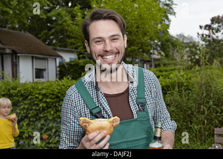 Germany, Cologne, Portrait of young man holding sausage and beer bottle while boy standing in background - Stock Photo