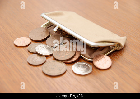 A purse filled with coins (British sterling money) spilling out onto a table - Stock Photo