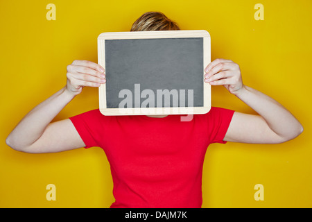 Young woman holding empty chalkboard in front of her face - Stock Photo