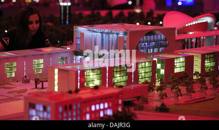 A staff member of the miniature world 'LOXX at Alex' views the red lighted miniature model of the chancellory in - Stock Photo