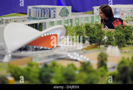 A staff member of the miniature world 'LOXX at Alex' views the miniature model of the chancellory in Berlin, Germany, - Stock Photo
