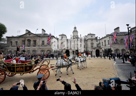Princess Catherine and Prince William ride in a horse-drawn carriage from Westminster Abbey to Buckingham Palace - Stock Photo