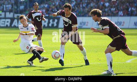 Gladbach's Marco Reus (L) kicks,  Hanover's Emanuel Pogatetz (C) intervenes. Reus later scores the 0-1 winning goal - Stock Photo