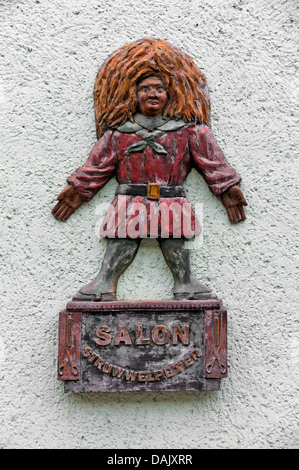Wooden relief, Struwwelpeter figure on a wall in front of a hair salon - Stock Photo