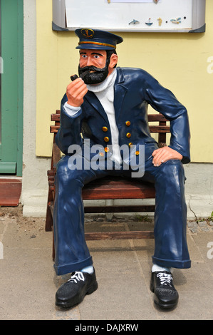 Life-size sailor figure on a bench in front of a house
