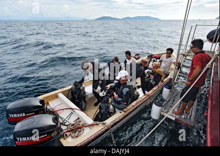 Scuba divers boarding the diving dinghy, Buginese Schooner, Seven Seas Liveaboard - Stock Photo