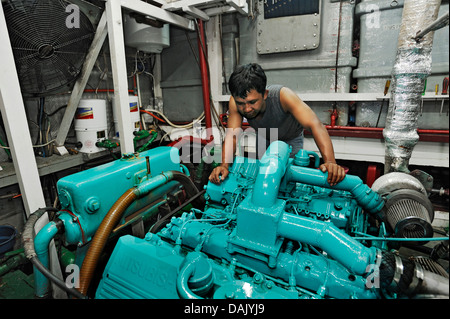 Machine operator in the engine room on the Buginese Schooner, Seven Seas Liveaboard - Stock Photo