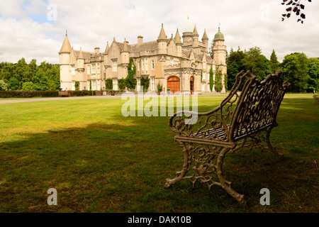 Horizontal view of Balmoral Castle, the Royal Family's summer residence, from garden on a sunny day with bench in - Stock Photo