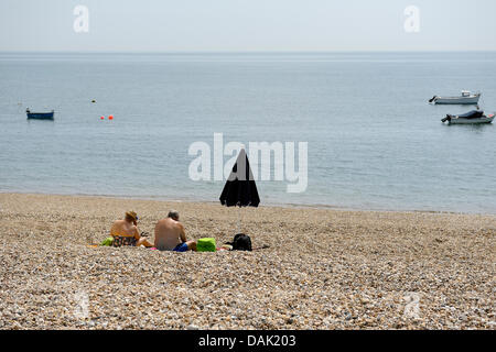 On one of the hottest days of the year an senior couple sit on a deserted west sussex shingle beach whilst enjoying - Stock Photo