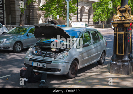 Man under car repairing it Victoria Embankment street central London England Britain UK Europe - Stock Photo
