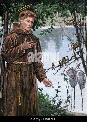 Saint Francis of Assisi addressing a group of birds. Hand-colored woodcut - Stock Photo