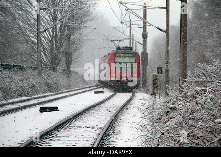S-Bahn during snowfall in winter, Germany, North Rhine-Westphalia - Stock Photo
