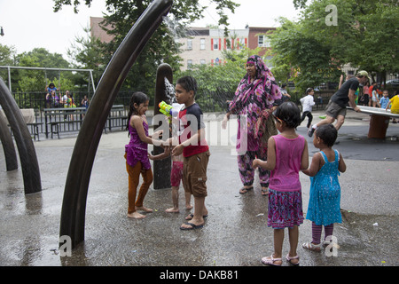 Children cool off at a playground on a summer day in Prospect Park in Brooklyn, NY. Muslim woman watches her children - Stock Photo