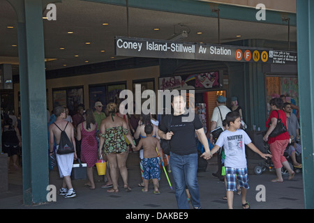 People leaving the Stillwell Avenue/Coney Island subway station along Surf Avenue in Brooklyn, NY. - Stock Photo