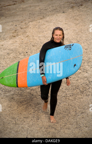 Wearing wetsuit and carrying surfboard, teenage girl member of the high school surfing team emerges from the Pacific - Stock Photo