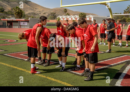 Multi-ethnic high school athletes stretch out during spring football practice in San Clemente, CA. Note coach. - Stock Photo