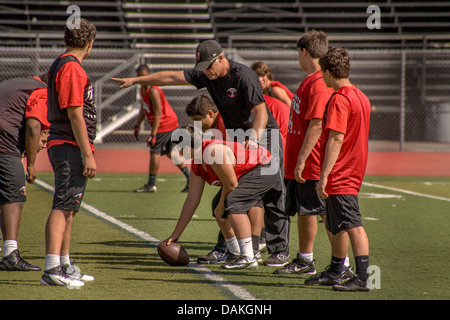 High school athletes get instructions during spring football practice in San Clemente, CA. - Stock Photo