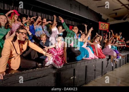 In 1950's clothing, the cast of a student production of the musical 'Grease' performs an ensemble number. - Stock Photo