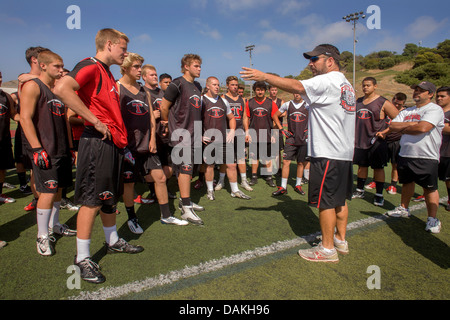 A high school coach gives a pep talk to his new team during spring football practice in San Clemente, CA. - Stock Photo