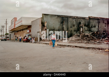 Hispanic locals walk past the ruins of a fire damaged shop in South Central Los Angeles after the 1992 Rodney King - Stock Photo