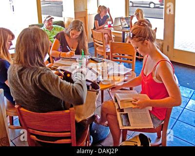 High school girls catch up on their homework at a Santa Barbara, CA, coffee shop - Stock Photo