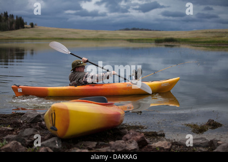 Young man in yellow orange kayak is paddling into a lake in Arizona with his feet and fishing pole propped up on - Stock Photo