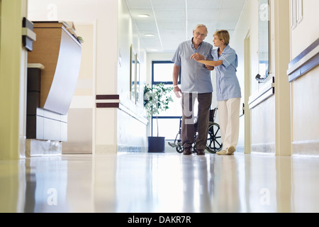 Nurse helping patient walk in hospital hallway - Stock Photo