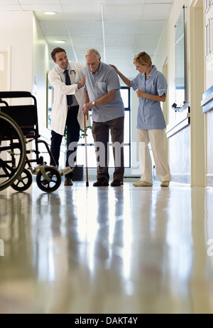 Doctor and nurse helping older patient walk in hospital - Stock Photo