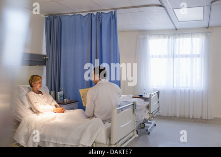 Doctor talking with patient in hospital room - Stock Photo