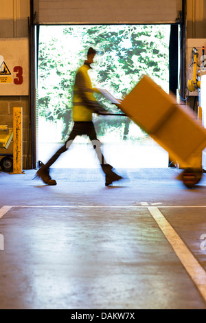 Blurred view of worker carting boxes in warehouse - Stock Photo