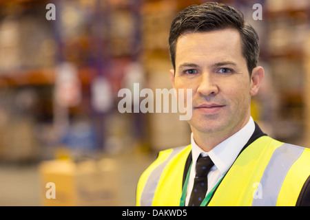 Businessman standing in warehouse - Stock Photo