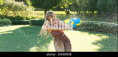 Girl playing with water gun in backyard - Stock Photo