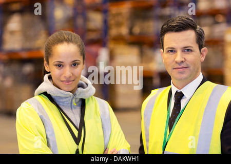 Businessman and worker smiling in warehouse - Stock Photo
