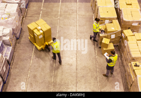 Workers carting boxes in warehouse - Stock Photo