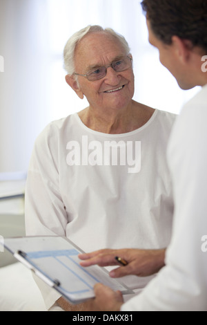 Doctor talking with older patient in hospital room - Stock Photo