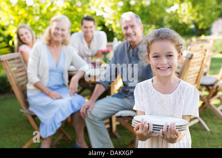Girl carrying plates to table outdoors - Stock Photo