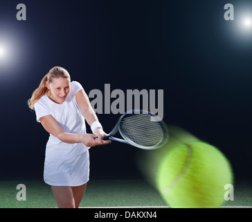 Tennis player hitting ball on court - Stock Photo