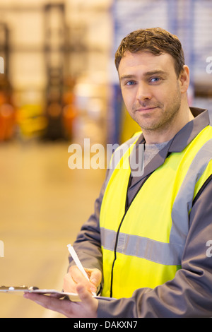 Worker using clipboard in warehouse - Stock Photo