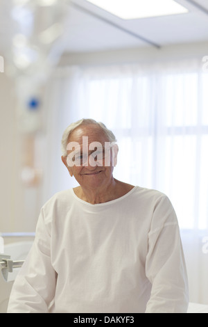 Older patient smiling in hospital room - Stock Photo