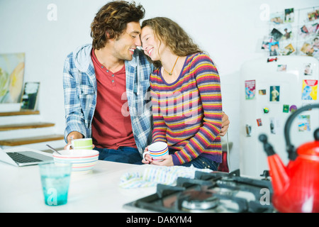 Couple relaxing together in kitchen - Stock Photo