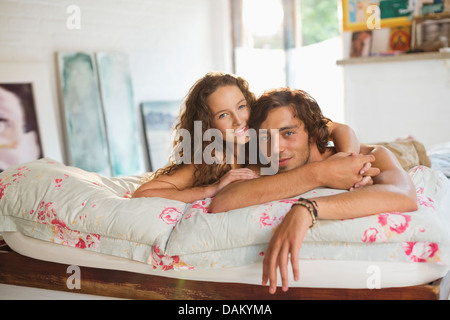 Couple relaxing together on bed - Stock Photo