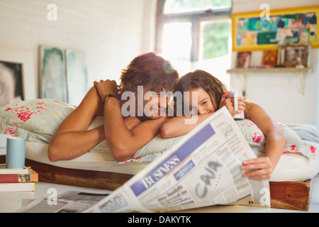 Couple reading newspaper together in bed - Stock Photo