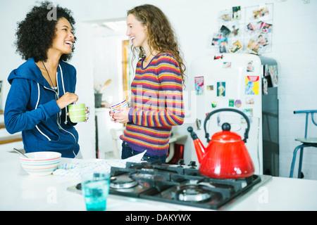 Women talking in kitchen - Stock Photo