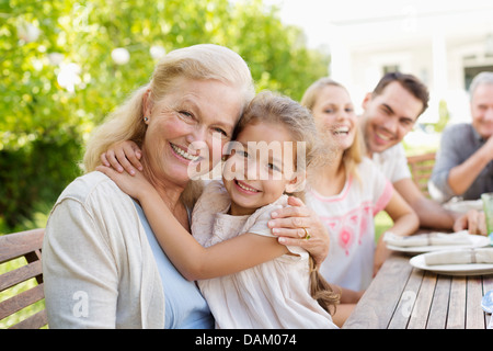 Older woman and granddaughter smiling outdoors - Stock Photo